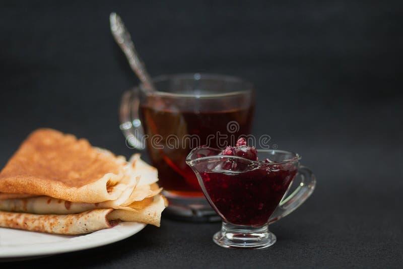 Thé avec la confiture et les crêpes de framboise Tasse de verre transparent, de sauce-bateau et de plat blanc Style foncé de phot photos stock