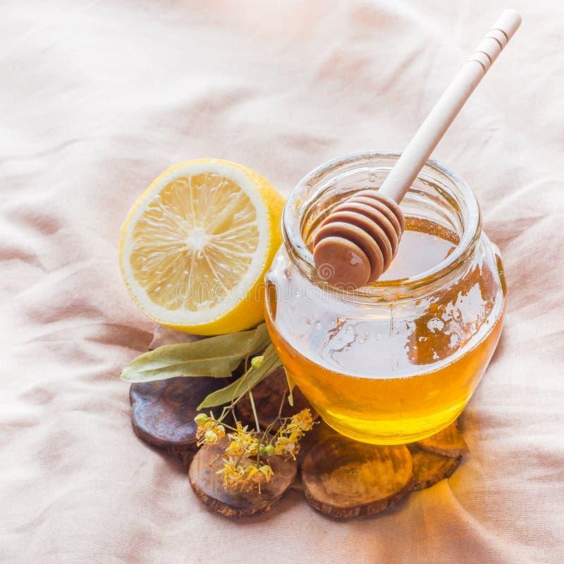 Thé avec le tilleul, le miel et le citron Le plateau sur le lit, le concept du traitement des froids photos stock