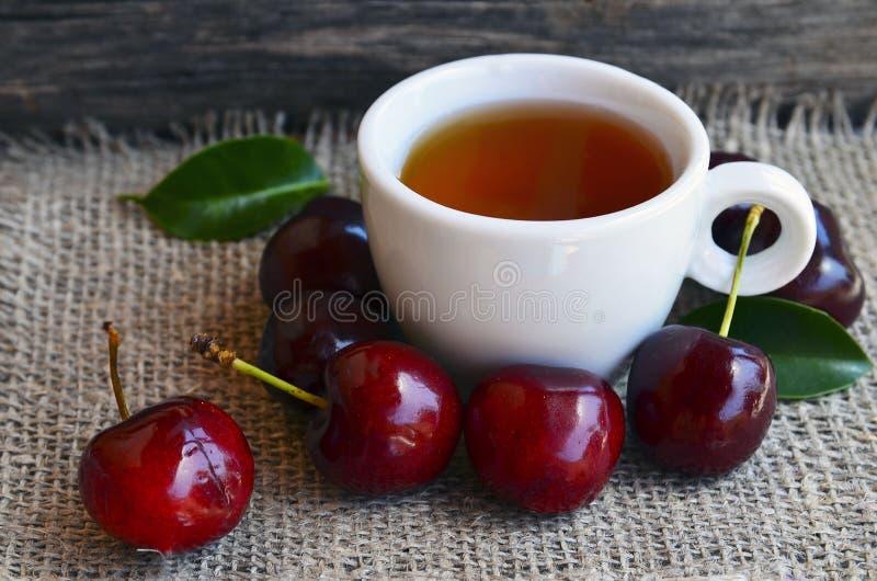 Thé avec les cerises fraîchement sélectionnées dans une tasse blanche sur un tissu de toile de jute Fruits de thé et de cerise de photos libres de droits