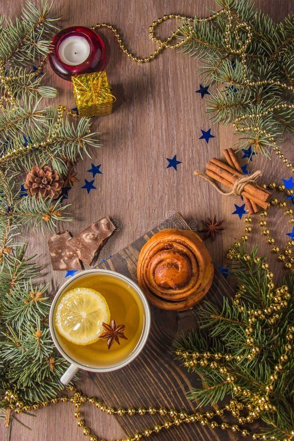 Thé avec les pâtisseries parfumées sur un fond en bois avec des décorations de Noël-arbre images stock