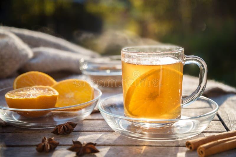Thé chaud de gingembre avec les tranches et les épices oranges sur un Tableau I en bois images stock
