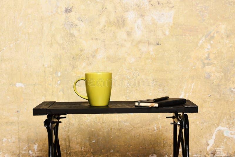 Thé chaud et fabrication du concept de notes Carnet avec le repère, le stylo et la tasse verte sur la table près du mur Thé ou ca photos stock