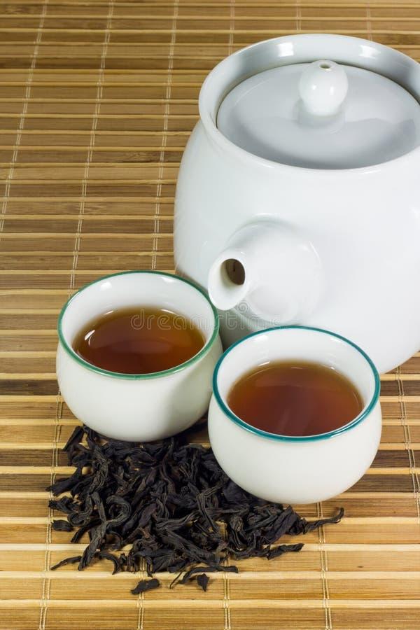Thé dans la tasse avec la feuille de thé photo stock
