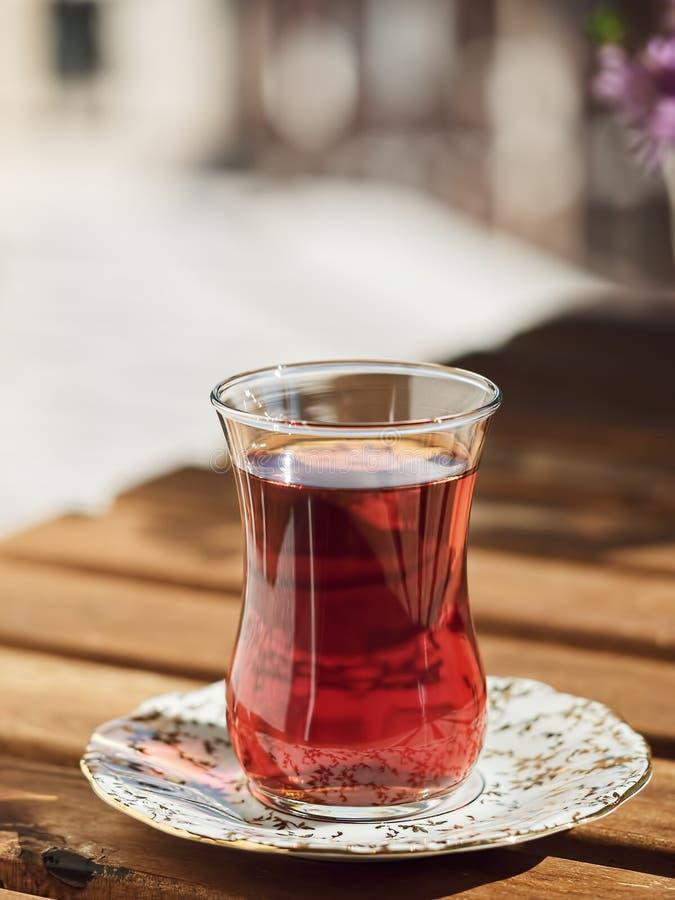 Thé dans un verre d'armudu sur une soucoupe, situé sur une table en bois dans la loggia Au fond, des fleurs Belle journée ensolei photos stock