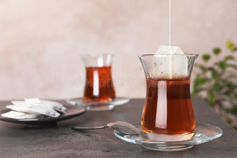 Thé de brassage avec le sac dans la tasse turque traditionnelle sur la table photos stock