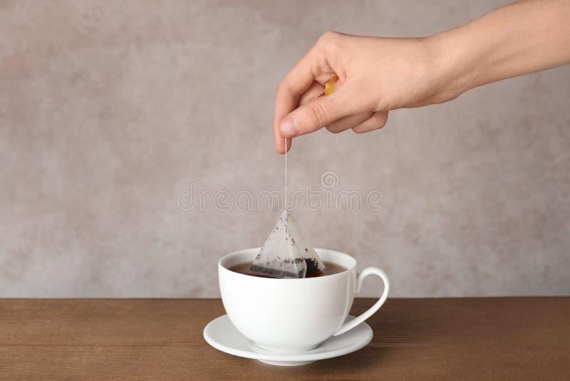 Thé de brassage de femme avec le sac dans la tasse sur la table image libre de droits