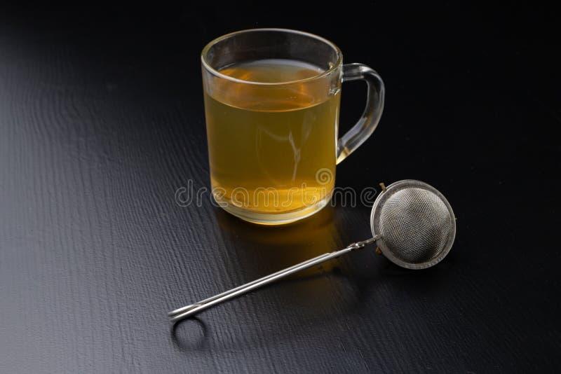 Thé de brassage sur une table noire Tasse avec une boisson chaude images stock
