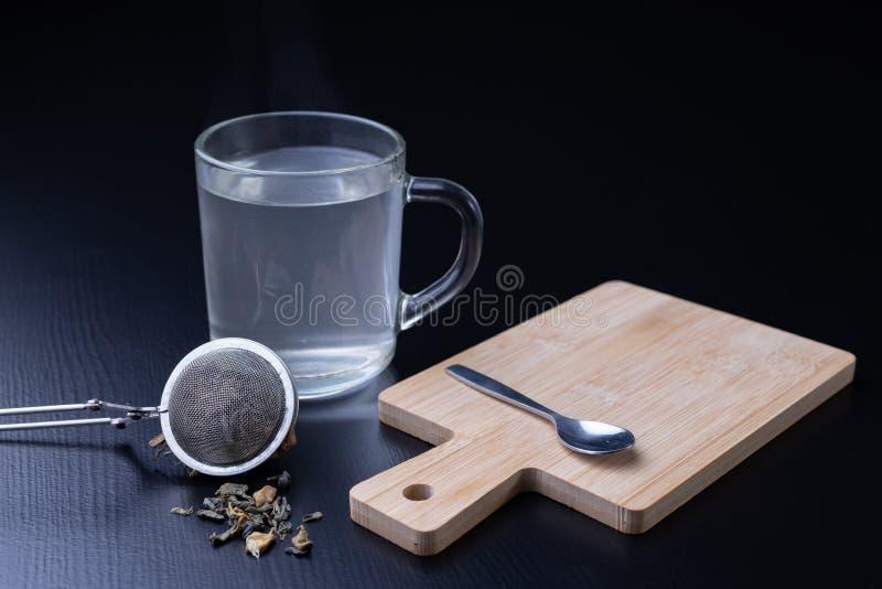 Thé de brassage sur une table noire Tasse avec une boisson chaude image stock