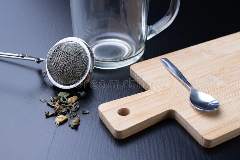Thé de brassage sur une table noire Tasse avec une boisson chaude photo libre de droits