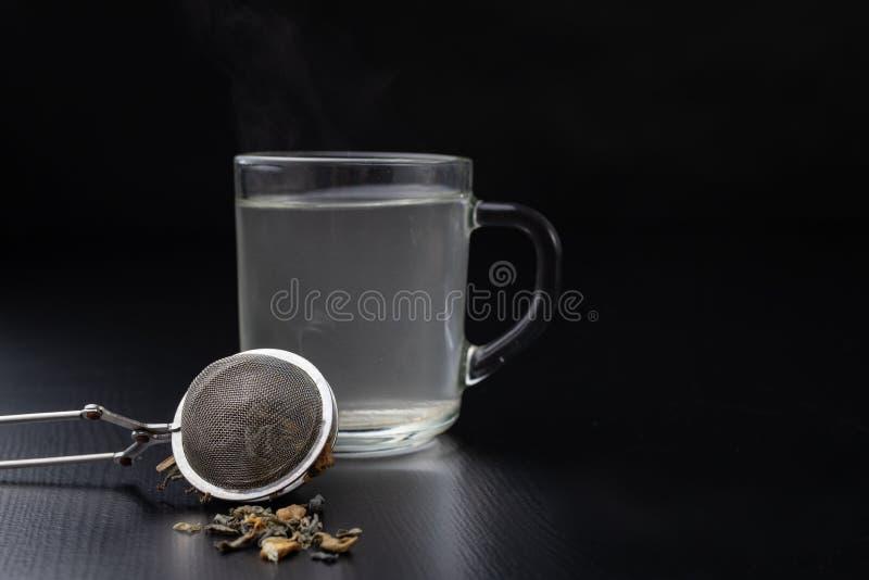 Thé de brassage sur une table noire Tasse avec une boisson chaude images libres de droits
