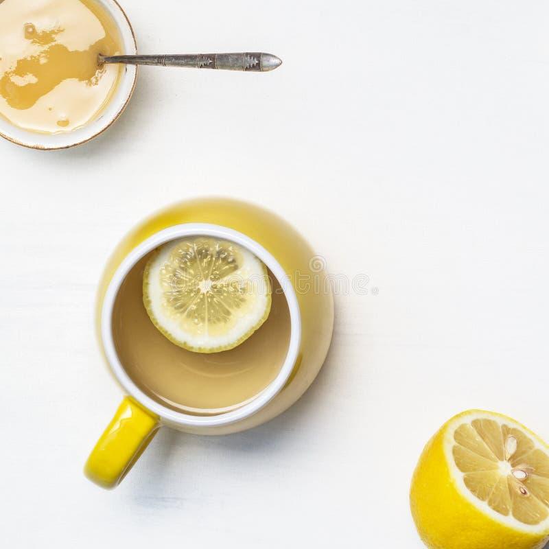 Thé de citron dans une tasse, un miel et une moitié jaunes d'un citron sur un fond blanc photographie stock libre de droits