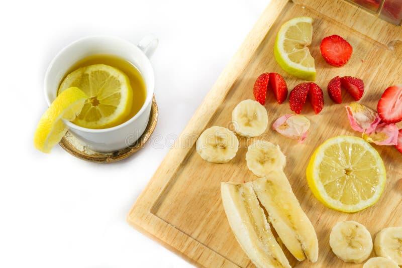 Thé de citron et citron, fraises et banane coupés en tranches sur le conseil en bois photographie stock
