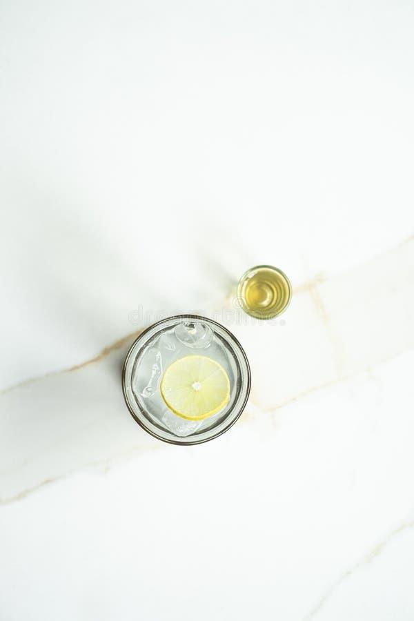 Thé de citron de glace avec du sucre liquide sur une surface blanche photographie stock