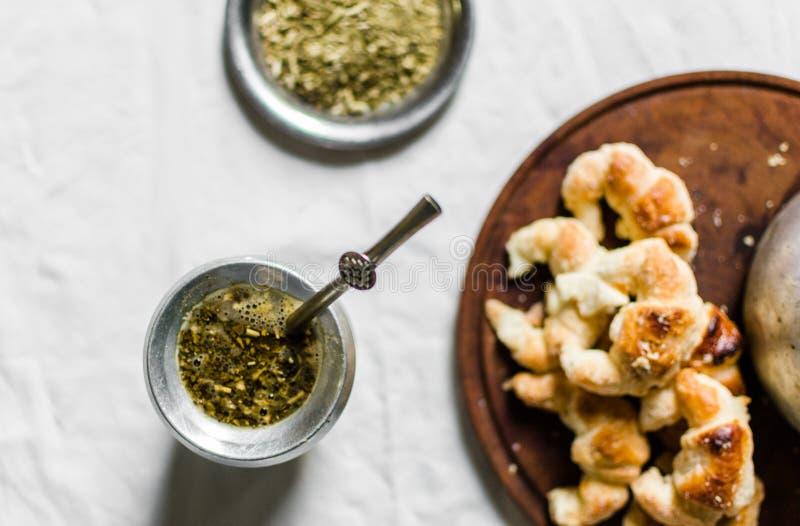 Thé de compagnon de Yerba, croissants sur un conseil en bois, et bouilloire sur le fond blanc photo stock
