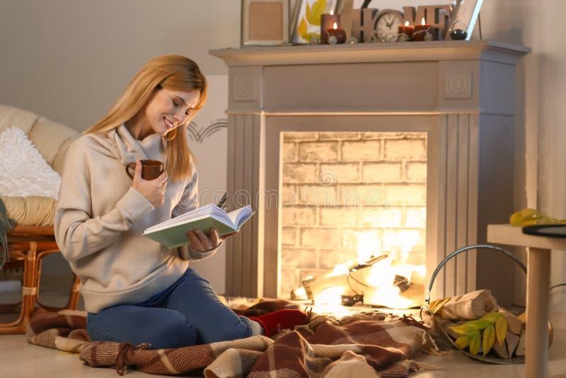 Thé de femme et livre de lecture potables près de cheminée image stock