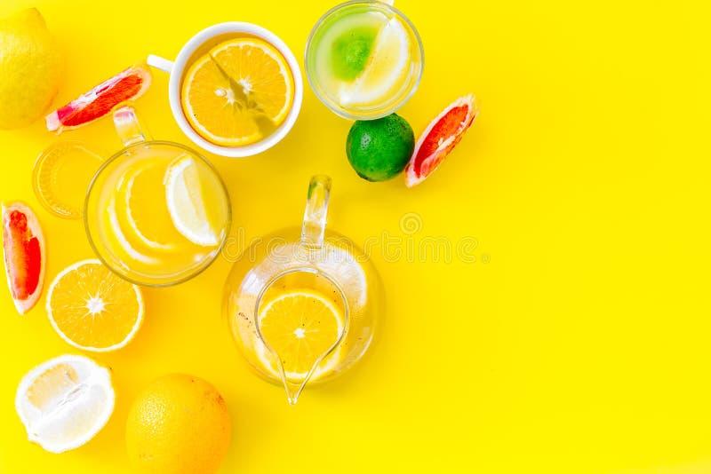 Thé de fruit d'infusion Tasse de thé et théière près d'orange, chaux, citron, pamplemousse sur l'espace jaune de vue supérieure d photographie stock
