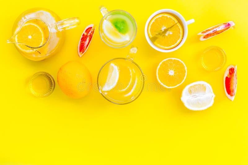 Thé de fruit d'infusion Tasse de thé et théière près d'orange, chaux, citron, pamplemousse sur l'espace jaune de vue supérieure d photo stock