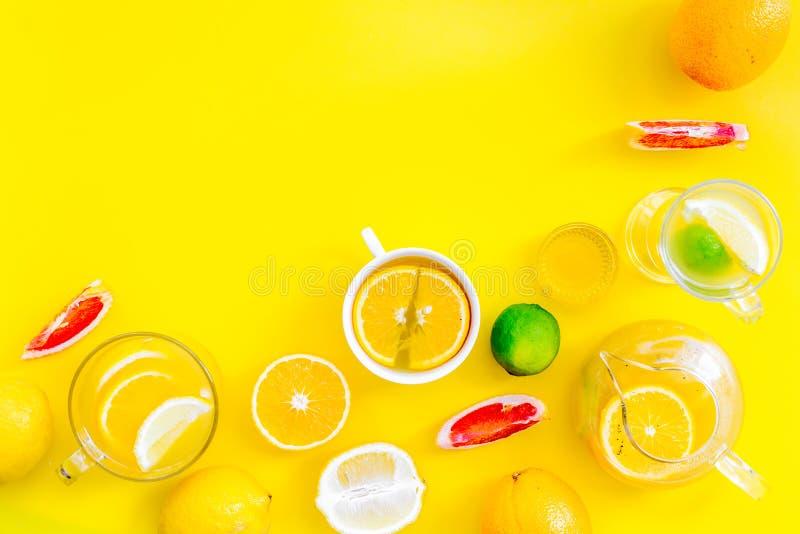 Thé de fruit d'infusion Tasse de thé et théière près d'orange, chaux, citron, pamplemousse sur l'espace jaune de vue supérieure d image stock