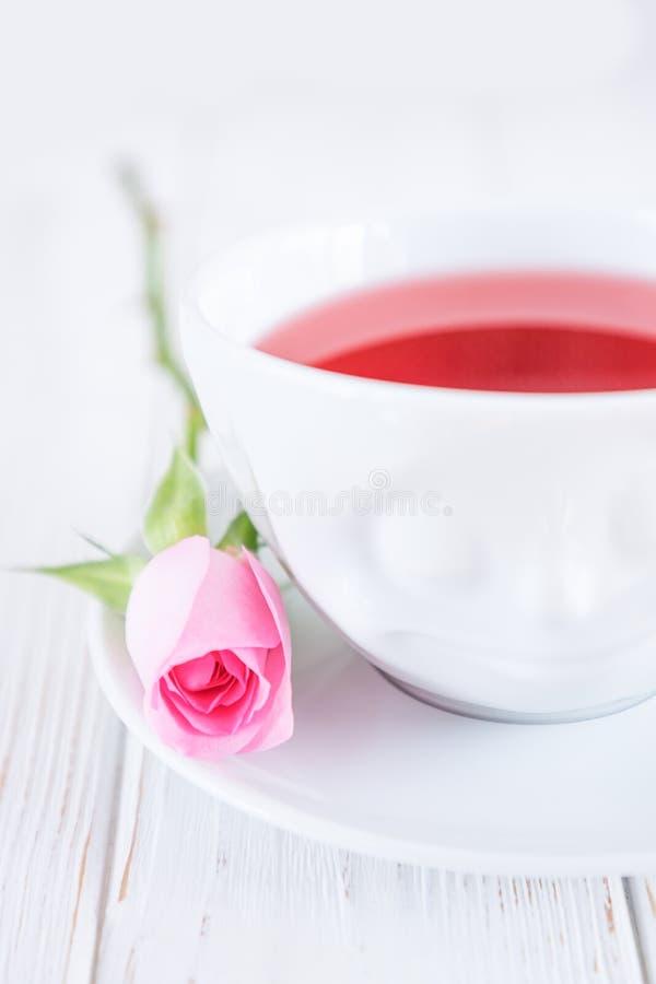 Thé de fruit dans la tasse et la rose blanches de rose sur un fond blanc L'espace libre photo libre de droits