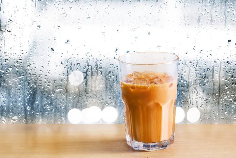Thé de lait glacé sur en bois et des gouttes de pluie sur le fond de miroir photos stock