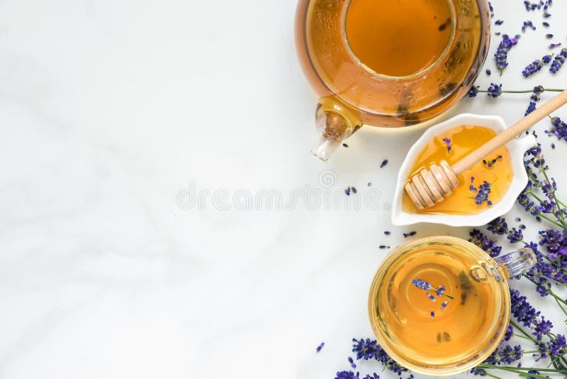 Thé de lavande dans une tasse et une théière avec du miel et les fleurs fraîches au-dessus de la table de marbre blanche Boisson  images stock