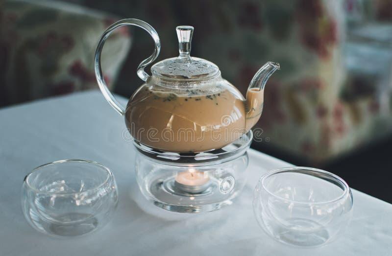 Thé de Masala dans une théière transparente image stock