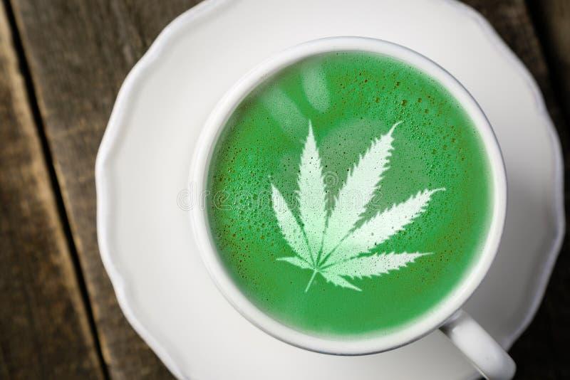 Thé de matcha de cannabis - feuille de marijuana sur la mousse de lait photo stock