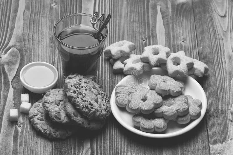 Thé et biscuits sur le fond en bois Concept chaud de boisson et de pâtisserie Glace de thé noir photographie stock libre de droits