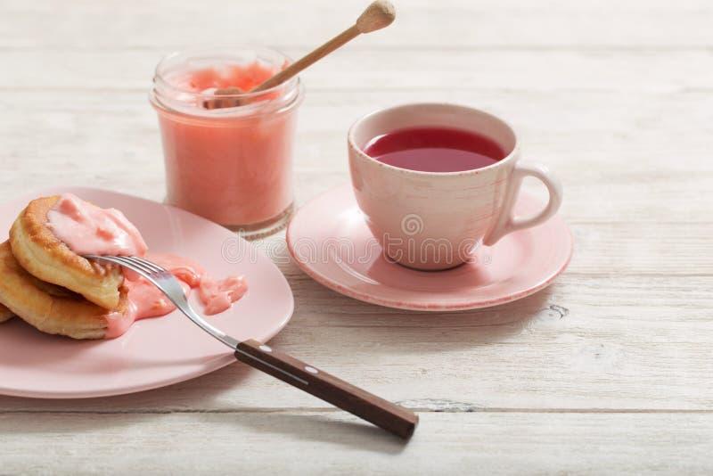 Thé et crêpes avec du miel rose de fruits sur la table en bois photographie stock