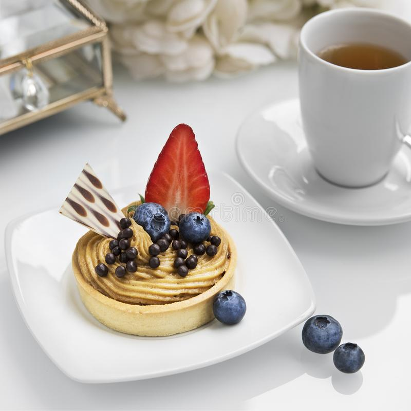 Thé et gâteau de Whate avec la fraise et les myrtilles des plats blancs sur une table blanche photographie stock libre de droits