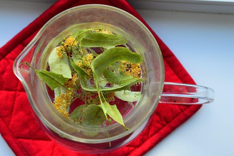 Thé fait de feuilles et fleurs fraîches de Tilia de petite taille-leaved Cordata de chaux dans le pot en verre sur le coussin rou image libre de droits