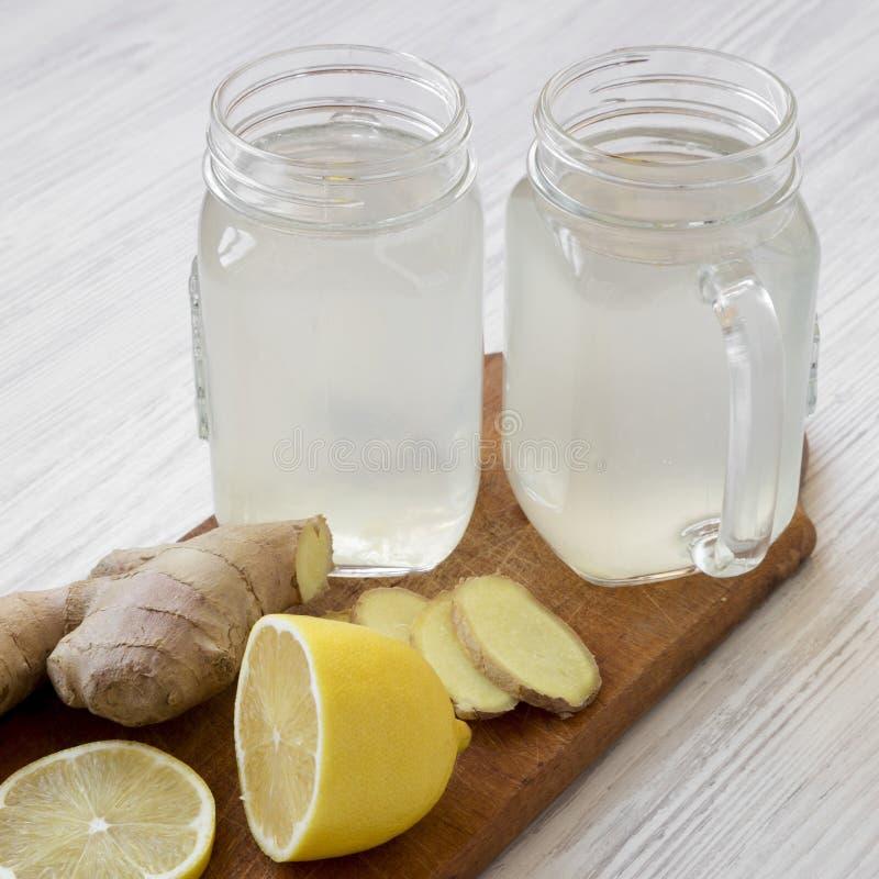 Thé fait maison de gingembre avec le citron dans des tasses en verre de pot sur un panneau en bois rustique, vue de côté Plan rap images stock