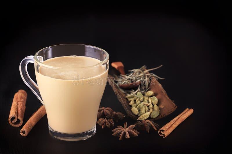 Thé indien chaud de lait avec des épices - cannelle, cardamome, gingembre, clous de girofle, poivron trapu et doux sur un fond no photographie stock libre de droits