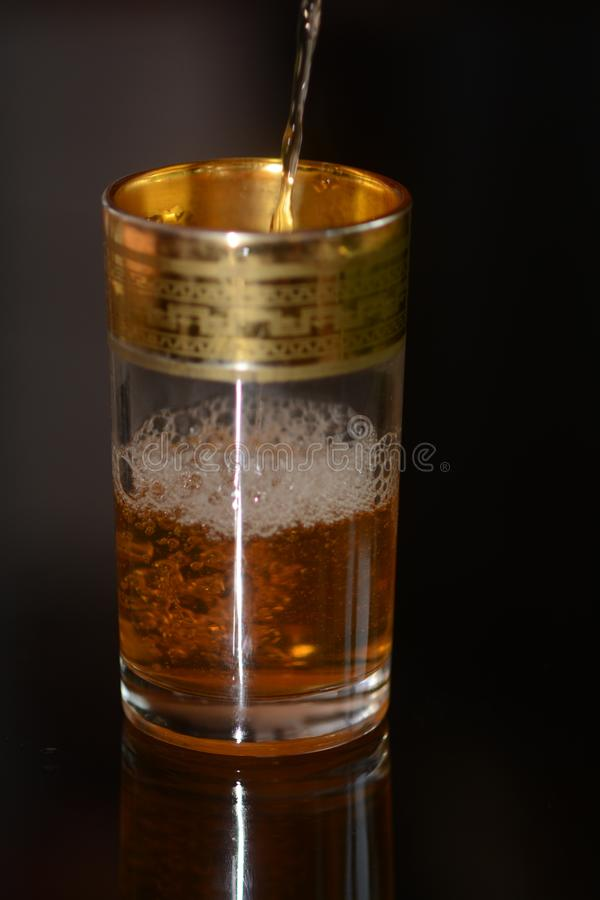Thé marocain versé dans le verre images stock