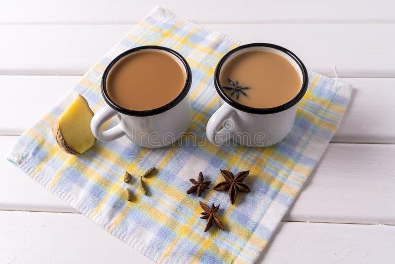 Thé Masala chai dans des tasses en aluminium, épices anis sur fond de table blanche image stock