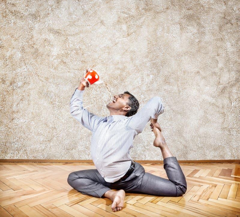 Thé potable d'homme d'affaires dans la pose de yoga images stock