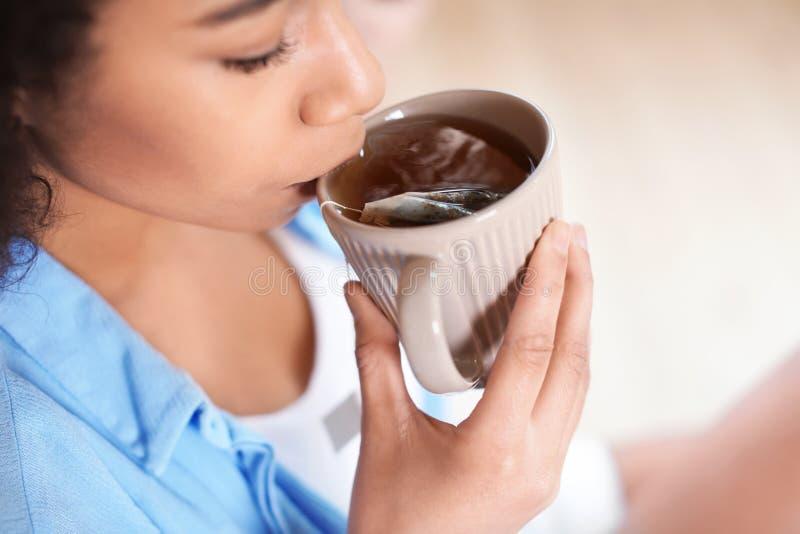 Thé potable de belle femme afro-américaine à l'intérieur, plan rapproché image stock