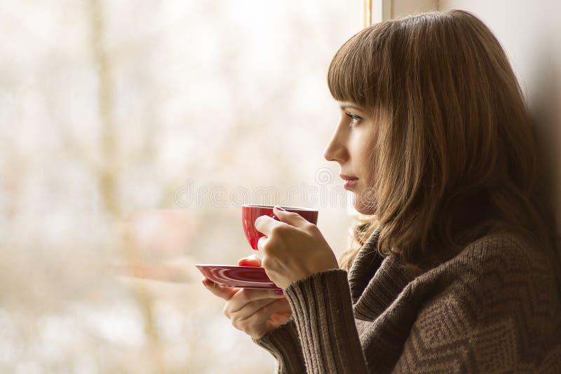 Thé potable de belle fille près de fenêtre photos stock