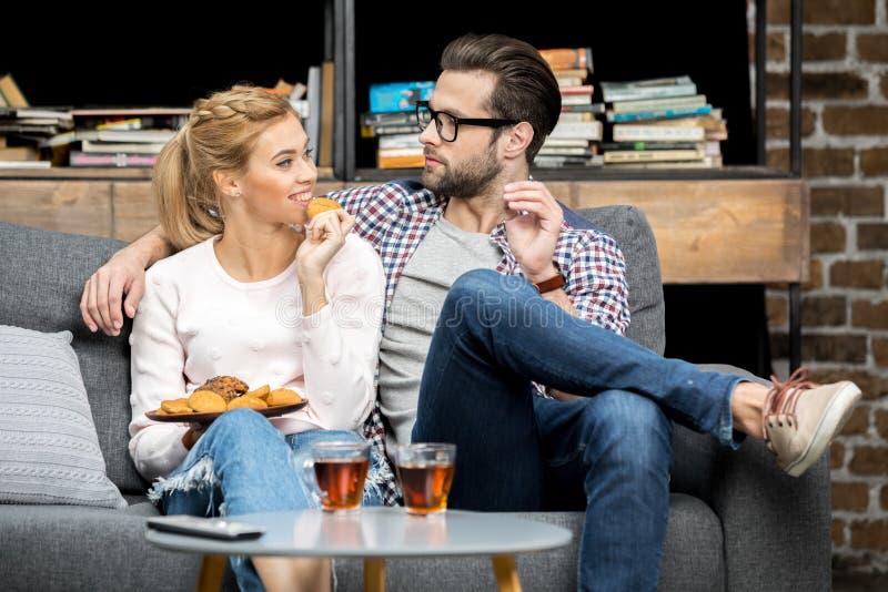 Thé potable de couples avec des biscuits images stock