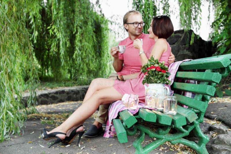 Thé potable de couples romantiques sur le banc photos libres de droits