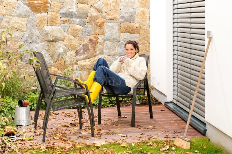 Thé potable de détente de patio d'automne de femme heureuse image stock
