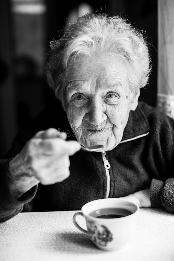 Thé potable de femme agée de portrait photo libre de droits