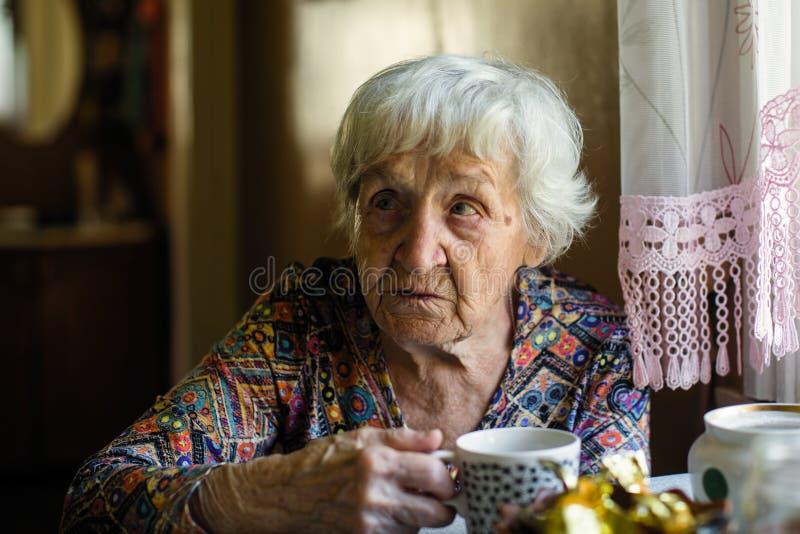 Thé potable de femme agée se reposant à la table jappement photographie stock