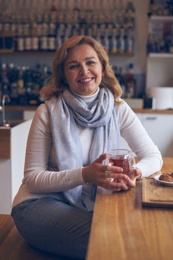 Thé potable de femme mûre décontractée en café photos stock