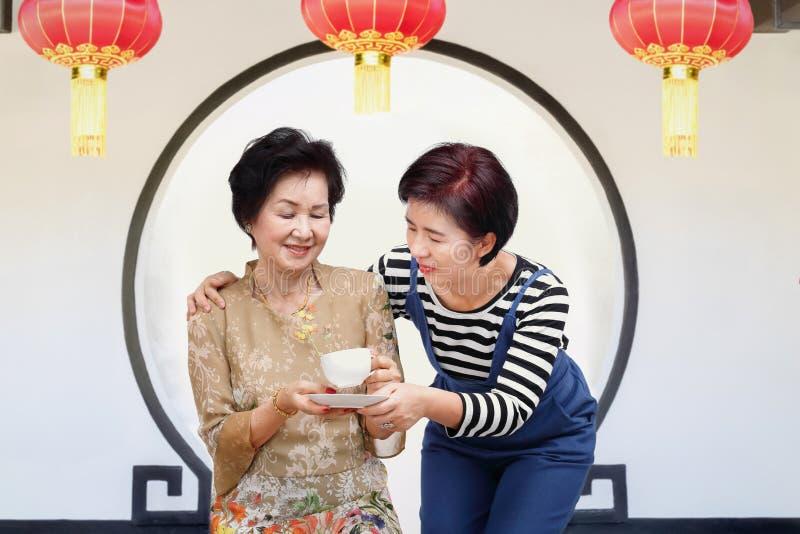 Thé potable de femme supérieure avec la fille dans le jardin traditionnel photo stock