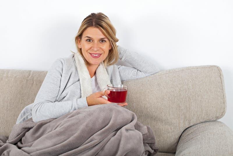 Thé potable de femme sur le sofa photo stock