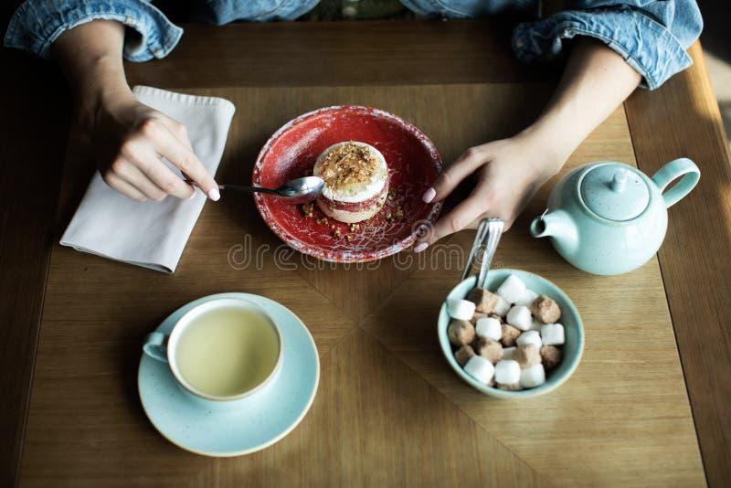 Thé potable de jeune fille avec le dessert délicieux image stock