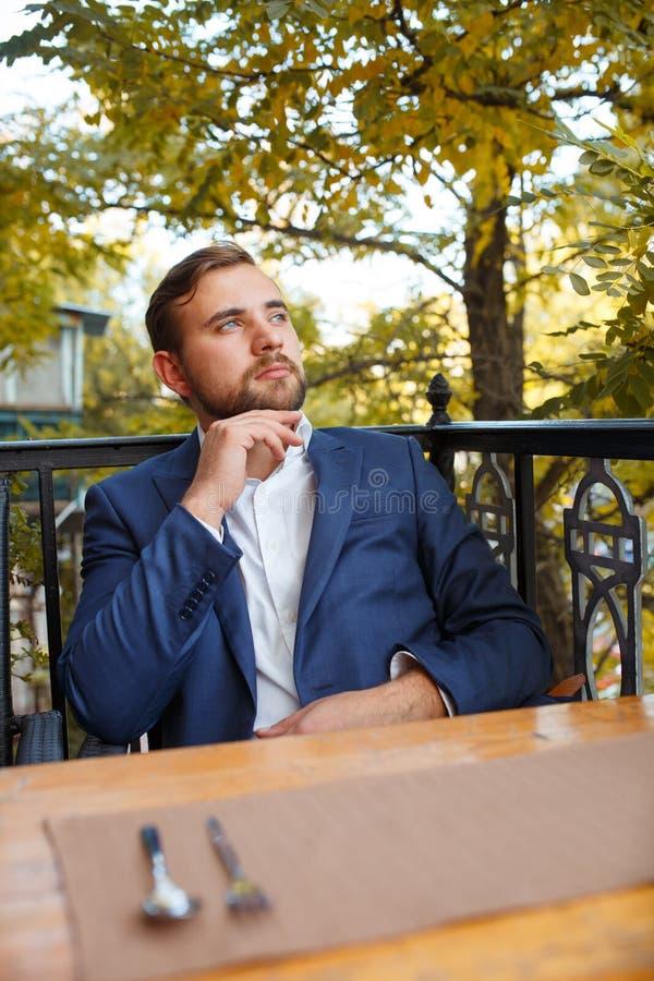 Thé potable de jeune homme avec des bonbons sur un fond naturel brouillé photographie stock