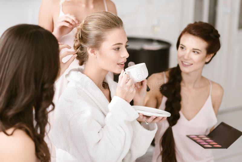 Thé potable de jeune jeune mariée agréable et être prêt photos stock