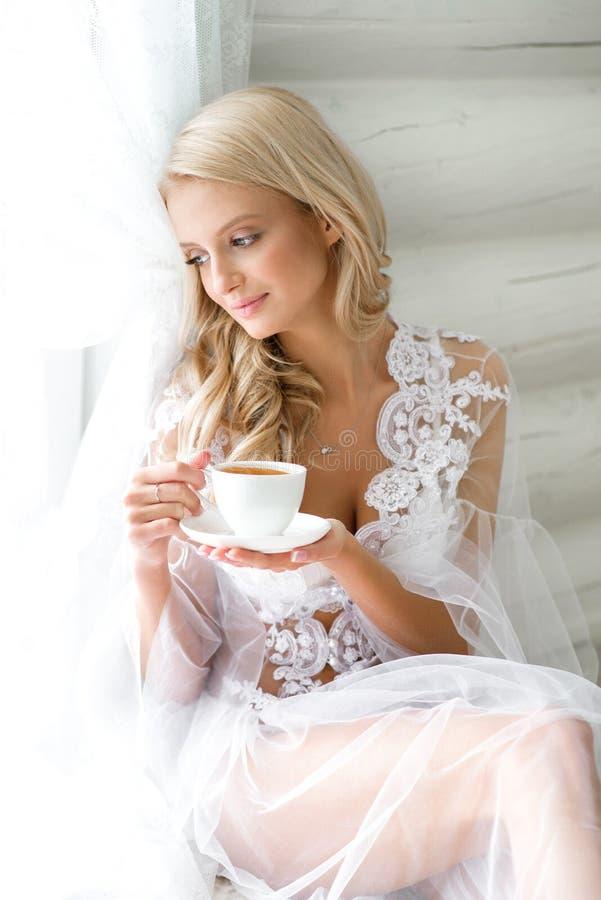 Thé potable de matin de fille dans la chambre à coucher image stock